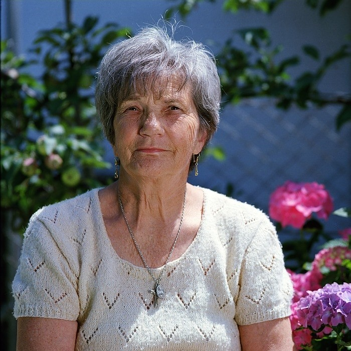 an elderly woman sitting by a flowerbed